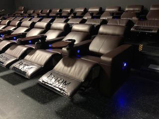 Apple Cinemas in Simsbury, Connecticut has installed nearly seven hundred Atom Seating Neon Recliners with swivel tables in eight auditoriums.