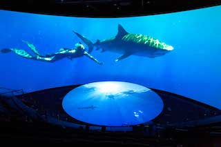 The new theatre has more than 300 seats and features an immersive 130-foot-wide by 32-foot-tall screen that curves in a 180-degree arc. A 30-foot-diameter disc tilts up from the floor to extend the projection surface